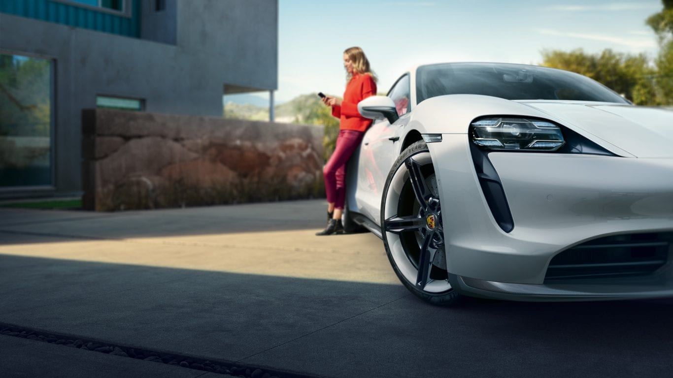 Nainen nojaa valkoiseen Porscheen
