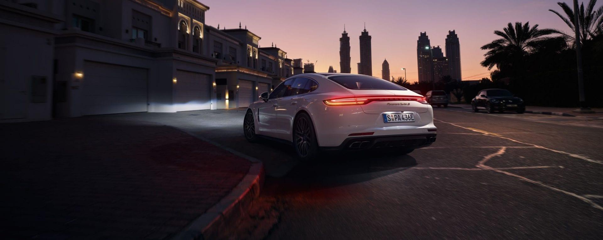 Porsche Panamera auringonlaskun aikaan kaupunkiympäristössä.