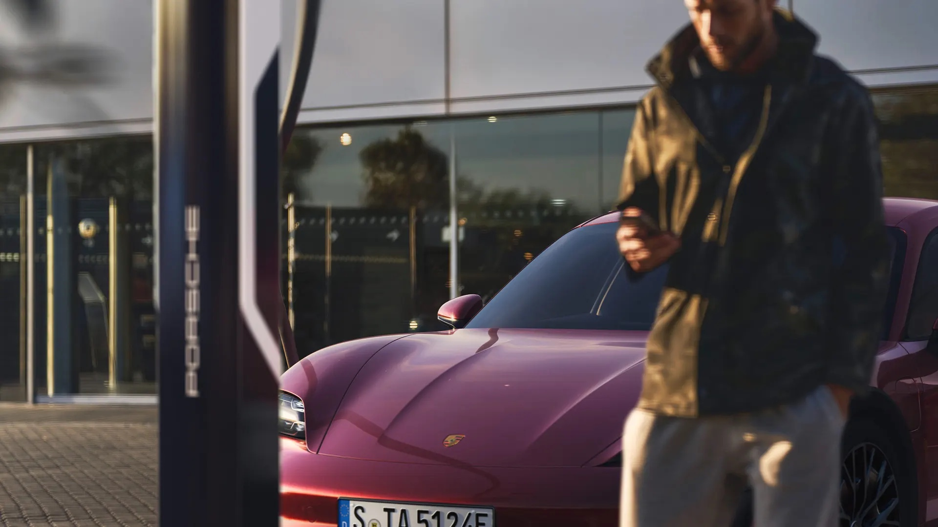 Mies katsoo kännykkää sähköauton latauspisteellä Taycan Cross Turismon edessä.