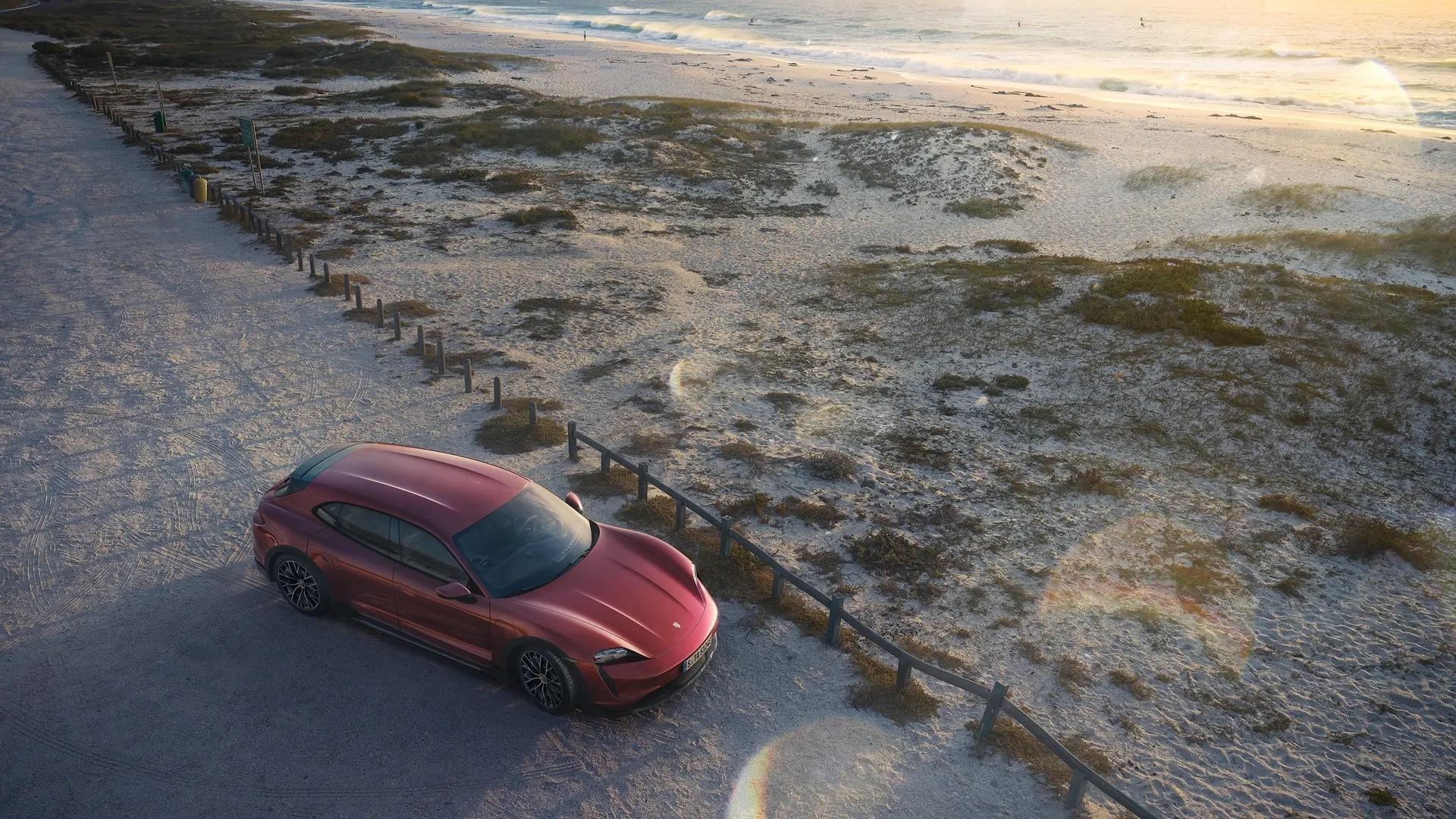 Taycan Cross Turismo ylhäältä päin pysäköitynä rannalle.